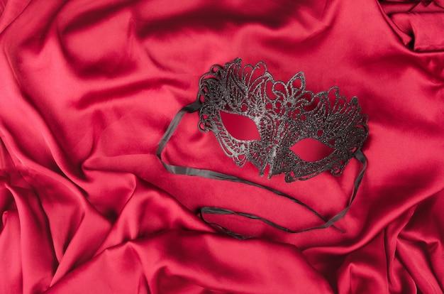Venezianische schwarze maske mit glitzer auf rotem seidenstoff