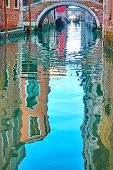 Venezianischer spiegel - häuser, blauer himmel und kleine brücke spiegeln sich im wasser eines seitenkanals. venedig in wasserreflexionen