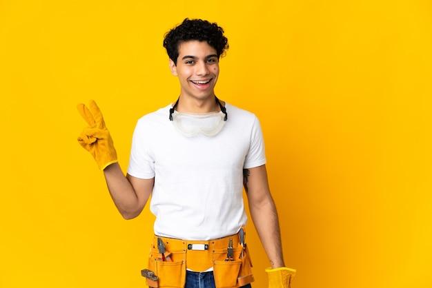 Venezolanischer elektriker auf gelbem lächeln und siegeszeichen zeigend