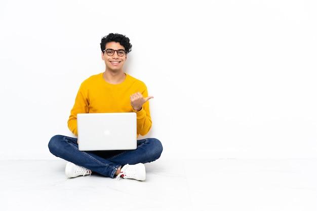 Venezolanischer mann sitzt auf dem boden mit laptop, der zur seite zeigt, um ein produkt zu präsentieren