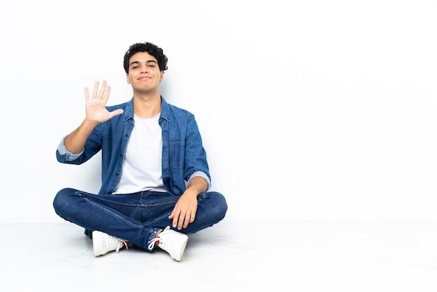Venezolanischer mann sitzt auf dem boden und zählt fünf mit den fingern