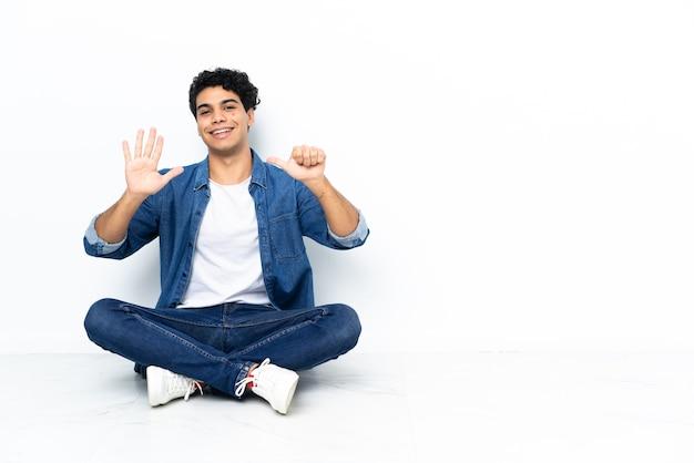Venezolanischer mann sitzt auf dem boden und zählt sechs mit den fingern
