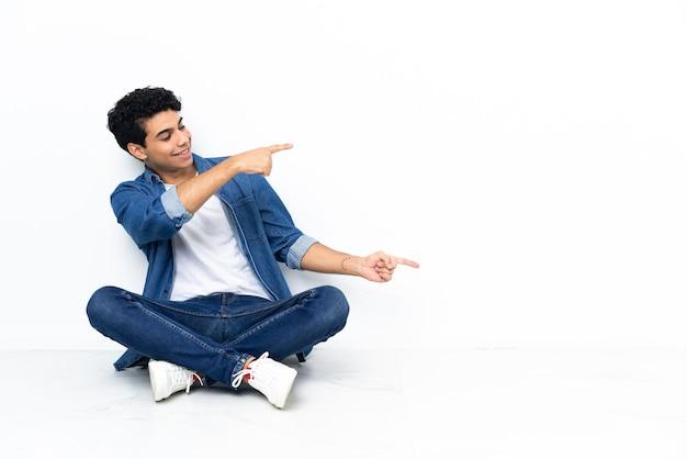 Venezolanischer mann sitzt auf dem boden und zeigt mit dem finger zur seite und präsentiert ein produkt