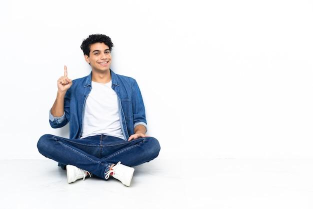 Venezolanischer mann sitzt auf dem boden und zeigt und hebt einen finger im zeichen des besten
