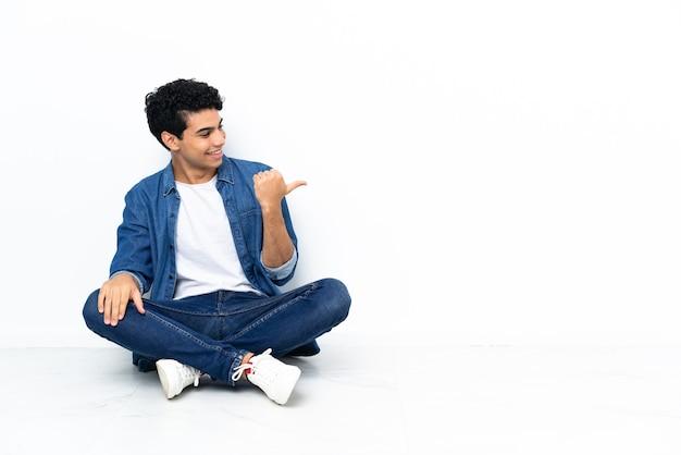 Venezolanischer mann sitzt auf dem boden und zeigt zur seite, um ein produkt zu präsentieren