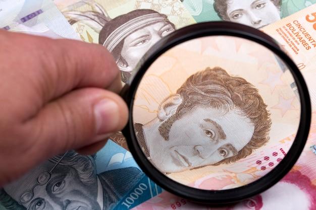 Venezolanisches geld in einer lupe ein geschäftshintergrund