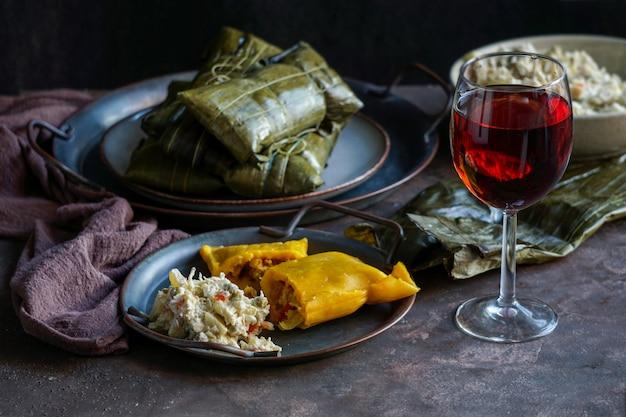 Venezolanisches weihnachtsessen, hallacas, maisteig gefüllt mit einem eintopf aus schweinefleisch und hähnchen-hähnchen-salat