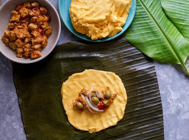 Venezolanisches weihnachtsessen, hallacas, maisteig gefüllt mit einem eintopf aus schweinefleisch und hühnchen