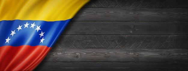 Venezuela flagge auf schwarzer holzwand. panorama.