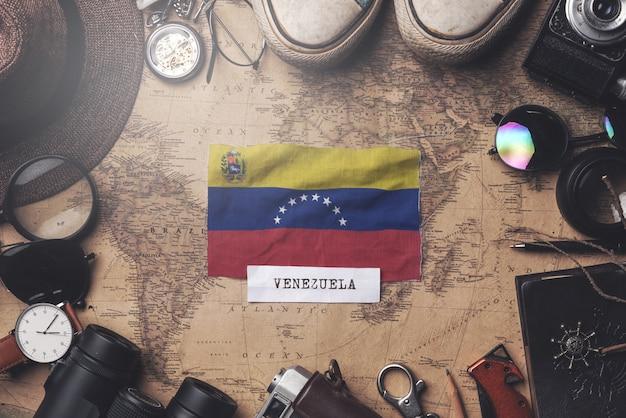Venezuela-flagge zwischen dem zubehör des reisenden auf alter weinlese-karte. obenliegender schuss