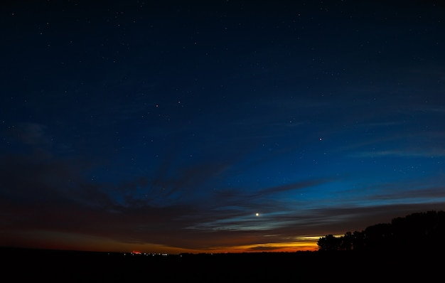 Venus am nachthimmel mit sternen. ein heller sonnenuntergang mit wolken. kosmischer raum über der erdoberfläche. langzeitbelichtung.