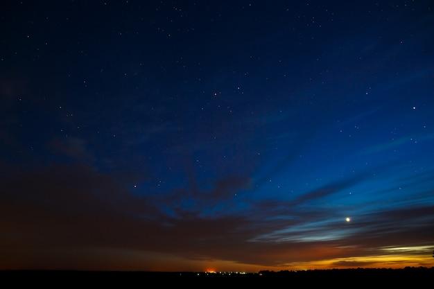 Venus am nachthimmel mit sternen. ein heller sonnenuntergang mit wolken. kosmischer raum über der erdoberfläche
