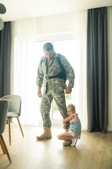 Verabschieden. mann verlässt sein zuhause für den militärdienst und verabschiedet sich von der kleinen emotionalen tochter