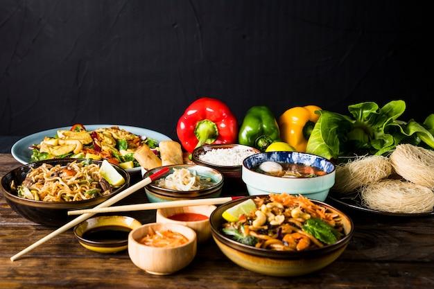 Veränderung der thailändischen küche mit grünem pfeffer und bokchoy auf hölzernem schreibtisch gegen schwarzen hintergrund