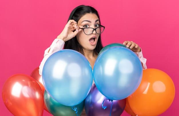 Verängstigt aussehende kamera junge schöne frau mit brille, die hinter luftballons steht, isoliert auf rosa wand