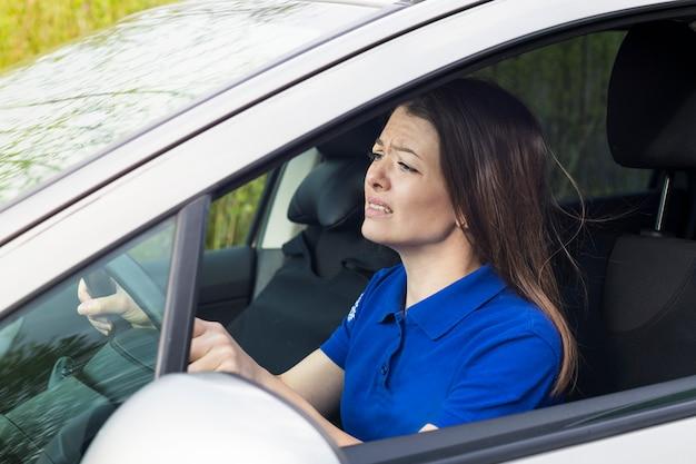 Verängstigte ängstliche frau, fahrer, junge verängstigte dame, die über einen verkehrsunfall schockiert ist, mädchen, das auto fährt, das lenkrad des autos hält. mit sicherheitsgurt gelöst. gefährliche situation auf der straße