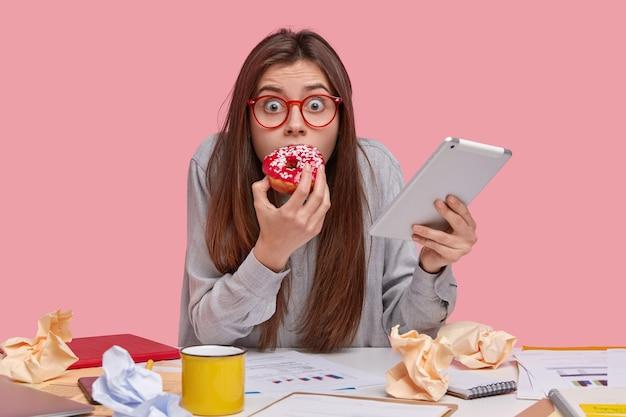 Verängstigte emotionale frau mit nervösen augen, isst gerne leckeren donut, hat angst, für schlechte arbeit bestraft zu werden, trägt ein modernes touchpad
