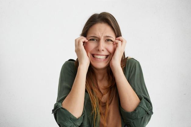 Verängstigte frau mit unangenehmem gesichtsausdruck runzelte die stirn und biss die zähne zusammen, um vor angst zu weinen. hübsche frau fühlt sich verärgert und sieht schockiert und stressig aus.