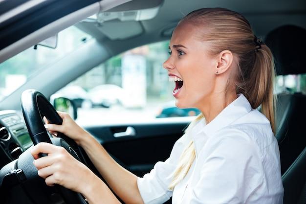 Verängstigte geschäftsfrau, die ihr auto fährt und schreit