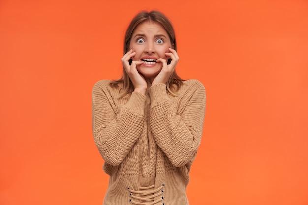 Verängstigte junge blauäugige weißköpfige frau mit kurzem haarschnitt, die ihre zähne zeigt und ängstlich die hände vors gesicht hebt, während sie über einer orangefarbenen wand steht