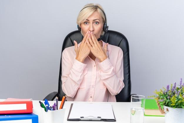 Verängstigte junge callcenter-betreiberin mit headset am tisch sitzend mit bürowerkzeugen bedeckten den mund mit den händen
