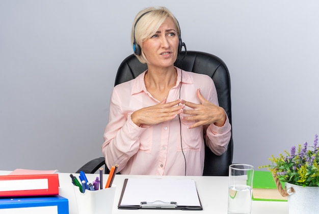 Verängstigte junge callcenter-betreiberin mit headset, die mit bürowerkzeugen am tisch sitzt