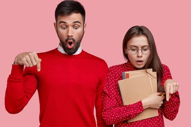 Verängstigte junge frau und mann mit erschrockenem gesichtsausdruck zeigen auf den boden, haben einen verwirrten blick, gekleidet in rotes outfit