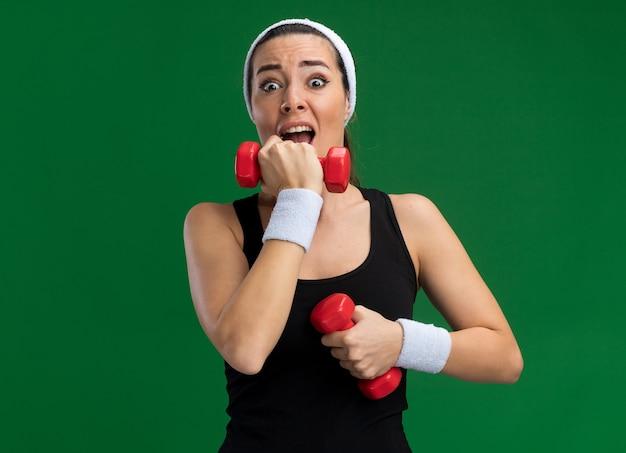 Verängstigte junge hübsche sportliche mädchen mit stirnband und armbändern, die hanteln halten und die hand am kinn halten, isoliert auf grüner wand mit kopierraum