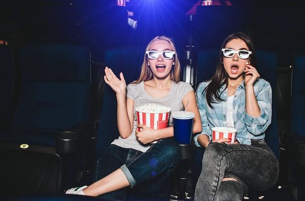 Verängstigte und aufgeregte mädchen sitzen in einem kinosaal und schauen filme. sie sind erstaunt. auch mädchen haben körbe mit popcorn und eine große tasse cola.
