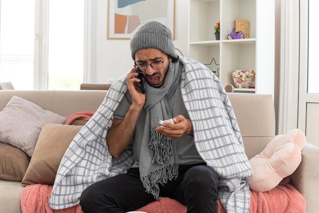 Verängstigter junger kranker kaukasischer mann in optischer brille, eingewickelt in plaid mit schal um den hals, der eine wintermütze trägt und am telefon spricht und auf das taschentuch schaut, das auf der couch im wohnzimmer sitzt?