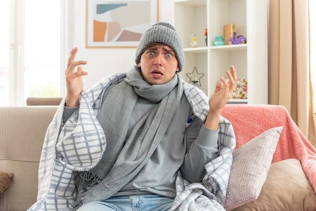 Verängstigter junger kranker mann mit schal um den hals, der eine wintermütze trägt, die in kariertes sitzen mit erhobenen händen auf der couch im wohnzimmer gehüllt ist