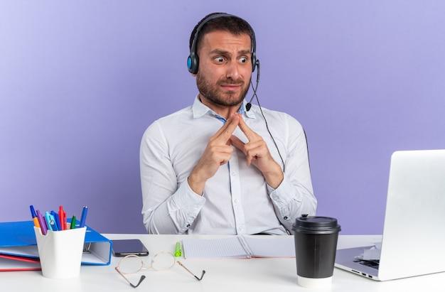 Verängstigter junger männlicher callcenter-betreiber mit headset am tisch sitzend mit bürowerkzeugen, die auf den laptop schauen