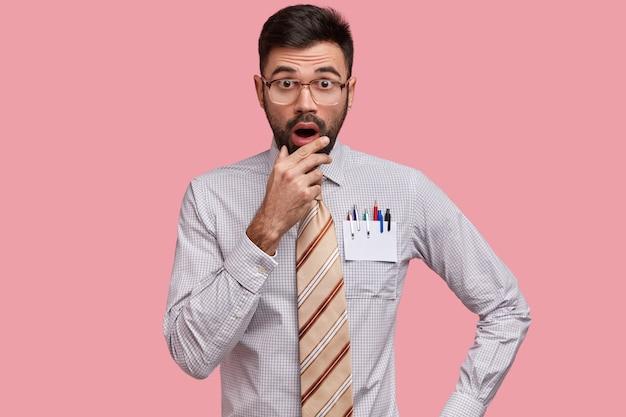 Verängstigter kaukasischer mann mit dunklen stoppeln, hält die hand am kinn, hat einen verblüfften ausdruck, trägt ein formelles hemd und eine gestreifte krawatte