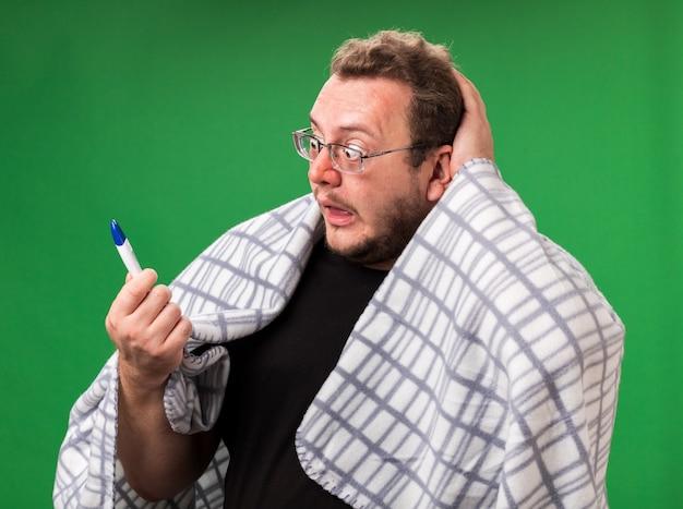 Verängstigter, kranker mann mittleren alters, eingehüllt in plaid, der das thermometer hält, packte den kopf