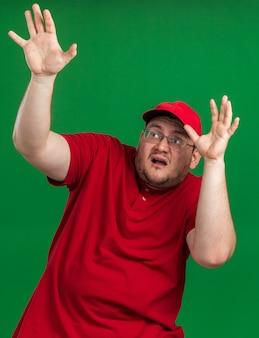 Verängstigter übergewichtiger junger lieferbote in optischer brille steht mit erhobenen händen, die isoliert auf grüner wand mit kopierraum nachschlagen