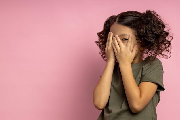 Verängstigtes asiatisches mädchen mit lockigem haar, im khaki-t-shirt, gesicht mit beiden handflächen bedeckend, versteckt, durch finger spähend, gruseligen cartoon beobachtend. menschliche gefühle. speicherplatz kopieren.