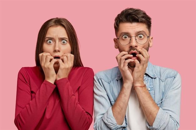 Verängstigtes junges paar, das gegen die rosa wand aufwirft