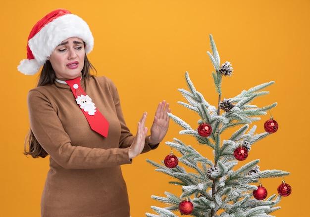 Verängstigtes junges schönes mädchen, das weihnachtsmütze mit krawatte trägt, die in der nähe des weihnachtsbaums steht und die hände am baum hält, isoliert auf oranger wand