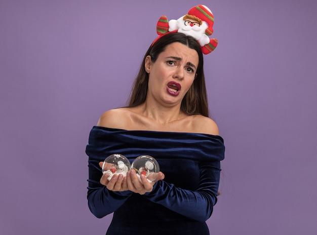 Verängstigtes junges schönes mädchen mit blauem kleid und weihnachtshaarreifen, das weihnachtskugeln isoliert auf lila wand hält