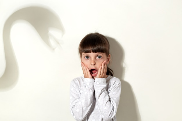 Verängstigtes kleines kind kleidet weiße freizeitkleidung und schreit laut, bedeckt die wangen mit handflächen und hat angst vor dem schatten einer riesigen schlange, die über einer grauen wand isoliert ist.