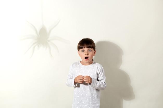 Verängstigtes kleines mädchen mit weißem freizeithemd, das wieder posiert. graue wand mit spinnenschatten, weibliches kind mit weit geöffnetem mund, bewegungslos stehend, insektenphobie.