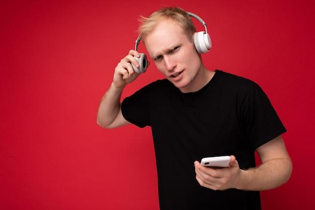 Verärgert, den gutaussehenden blonden jungen mann mit schwarzem t-shirt und weißen kopfhörern zu fragen, der isoliert auf rotem hintergrund steht, mit kopienraum, der smartphone hält und online musik hört a