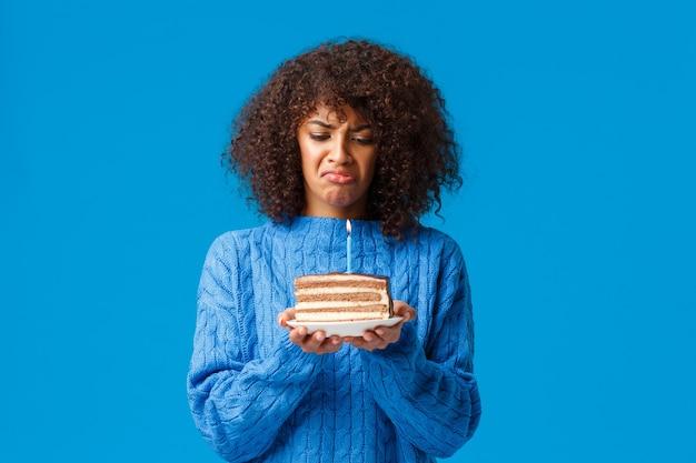 Verärgert und düster, verzweifelte junge afroamerikanische frau hassen es, geburtstag zu feiern, sich älter zu fühlen, belästigt und unzufrieden mit geburtstagstorte mit brennender kerze, schmollender, blauer wand.