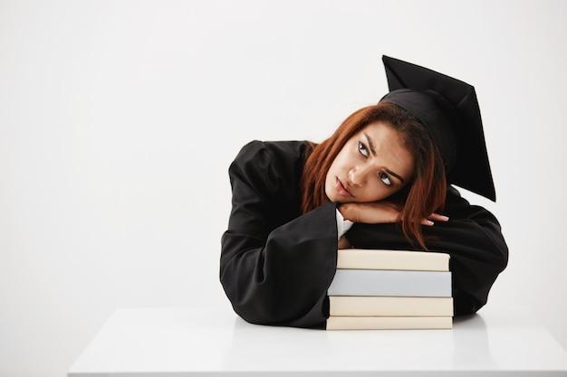 Verärgert und müde vom studium der afrikanischen studentin und des zukünftigen absolventen, der auf büchern liegt, die über beruf und diplomsitzen nachdenken. speicherplatz kopieren.