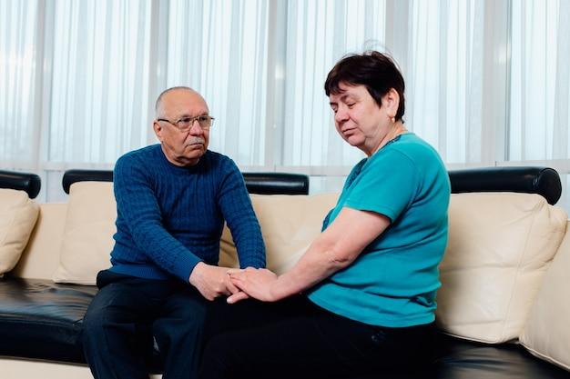 Verärgerte ältere familie grauhaariger ehemann hilft bei der überwindung von problemen, unterstützt unglückliche reife frau zu hause, sitzt auf der couch, weint nach streit mit mann