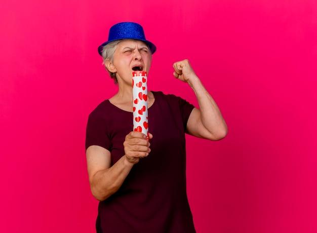 Verärgerte ältere frau, die partyhut trägt, hält konfettikanone und hält faust mit geschlossenen augen auf rosa