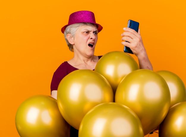 Verärgerte ältere frau, die partyhut trägt, steht mit heliumballons, die telefon lokalisiert auf orange wand betrachten