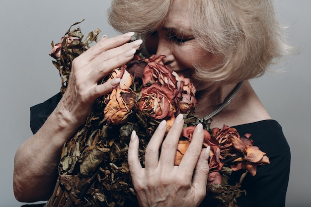 Verärgerte ältere frau, die weint und verwelkten trockenen alten rosenblumenstrauß hält