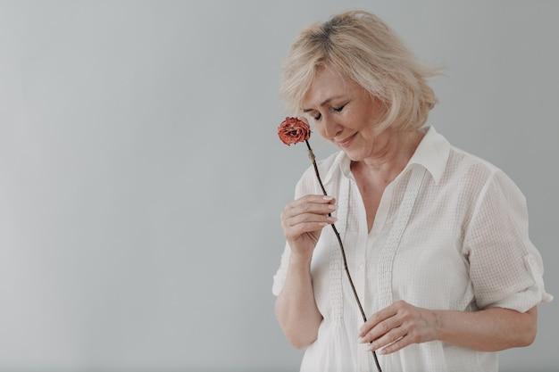 Verärgerte ältere frau im weiß gekleideten griff verdorrte eine trockene alte rosenblume.