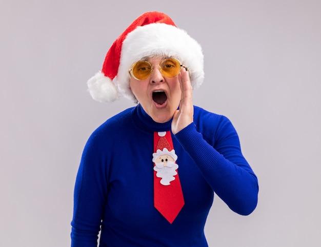 Verärgerte ältere frau in sonnenbrille mit weihnachtsmütze und weihnachtskrawatte hält hand nah am mund und ruft jemanden an
